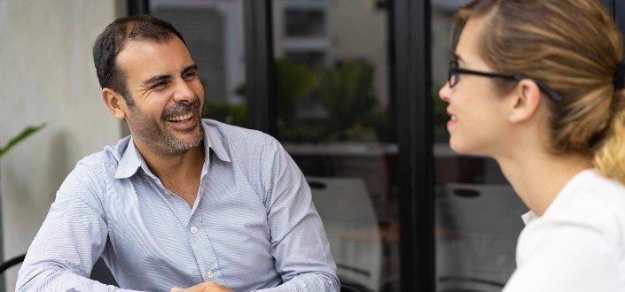 Hombre hablando y sonriendo a una mujer con gafas
