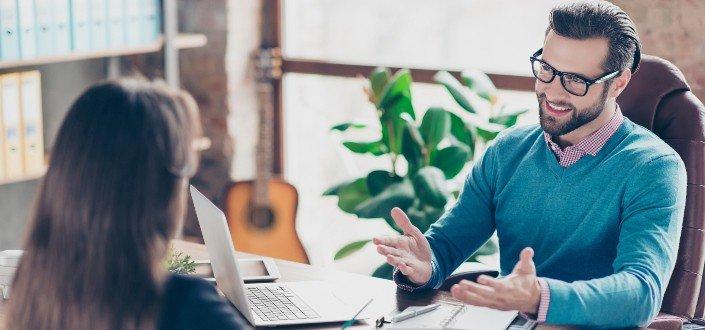Un empleador masculino entrevistando a una solicitante femenina