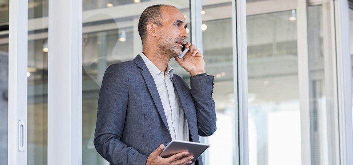 Hombre de negocios hablando por teléfono mientras sostiene una tableta