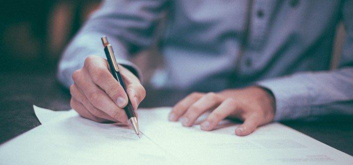 Una persona que escribe en un papel