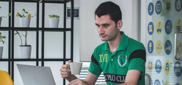 Hombre sujetando una taza de café mientras mira portátil