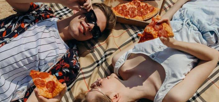 Pareja acostado en una manta y comiendo pizza
