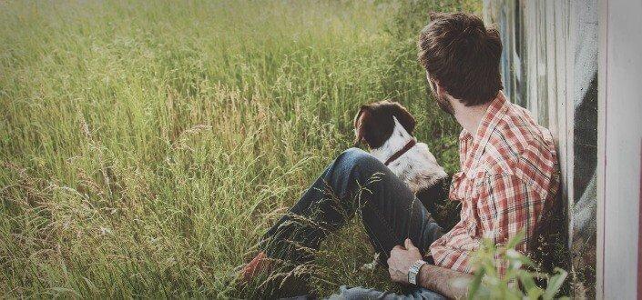 Guy y su perro sentados en el césped