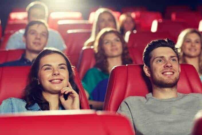 Amigos felices viendo peliculas en teatro