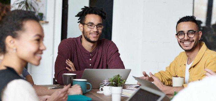Tres personas en una reunión sonriendo