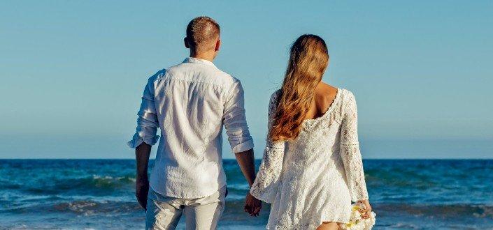 Pareja cogidos de la mano y frente a la playa