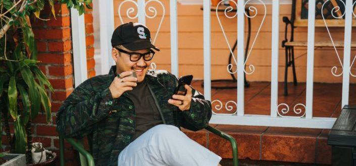 hombre riendo sentado en una silla mientras usa el teléfono inteligente