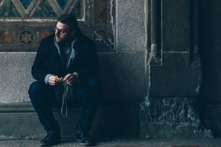 hombre sentado en un callejón con auriculares en una mano