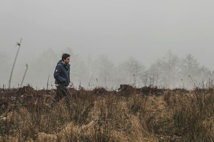 El hombre con las manos en el bolsillo caminando sobre un campo seco